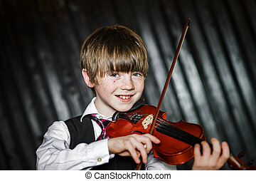 Attractive boy playing violin, studio shooting, music ...