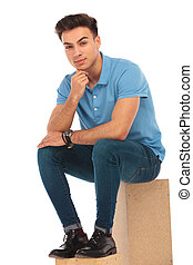 attractive boy seated on box
