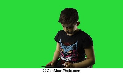 Attractive boy using tablet pc while standing on green chroma key background