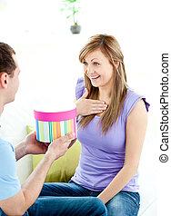 Attractive boyfriend giving a present to his pretty girlfriend