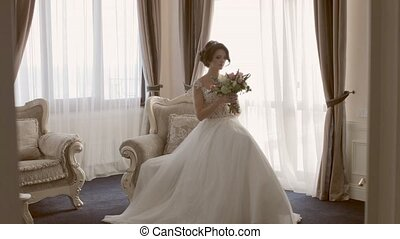Attractive bride sitting in the chair with the bouquet in hands