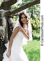 Attractive Bride stands about trees in the park