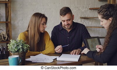 Attractive broker is selling house to young couple, people are signing documents and shaking hands, realtor is giving key to new owner, he is kissing his wife.