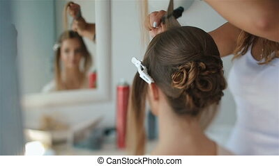 Attractive brunette bride looks in the mirror while doing her hairstyle