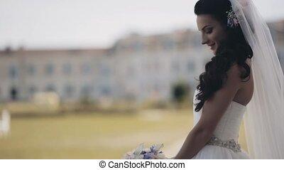 Attractive brunette bride standing in nature wearing the...