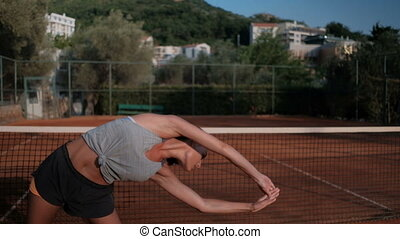Attractive brunette doing lateral bends exercise standing in stadium on summer day.