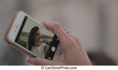 Attractive brunette doing selfie on her mobile phone