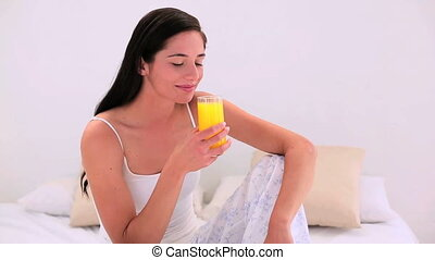 Attractive brunette drinking a glass of juice