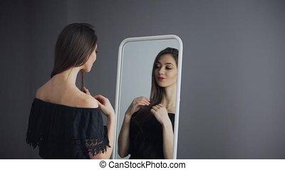 Attractive Brunette Girl Looking in Mirror