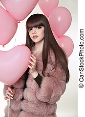 Attractive brunette girl with long healthy hair in fur fox coat posing with pink balloons isolated on studio white background