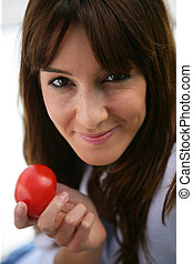 Attractive brunette holding a tomato