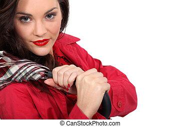 Attractive brunette holding umbrella over shoulder