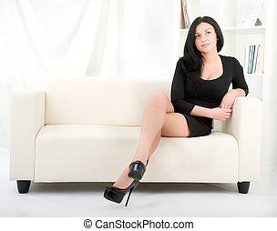 brunette in a black dress on a sofa