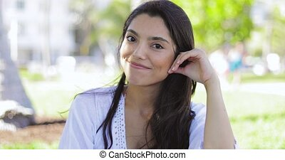 Attractive brunette in summertime looking at camera -...