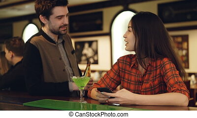 Attractive brunette is checking smartphone at bar counter when young man is getting acquainted with her. Young people are chatting, smiling and clinking glasses.