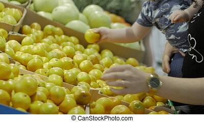 Attractive brunette lady with a little baby boy in his arms chooses fruits - mandarins - in the supermarket. Shopping and people concept. Stock video footage.