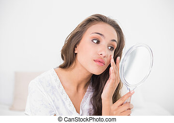 Attractive brunette looking closely at mirror