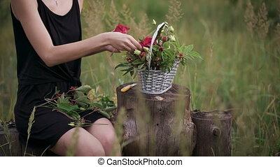 Attractive brunette making a flower arrangement of roses....