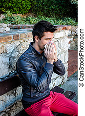 Attractive Brunette Man With Red Pants Blowing He's Nose