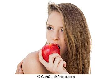 Attractive brunette model eating an apple on white ...