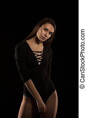 Attractive brunette model in black underwear posing in the shadows