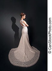 Attractive brunette model in white wedding dress standing on the background of a dark wall