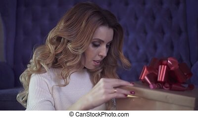 Attractive brunette opens gift