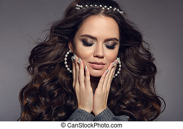 Attractive brunette portrait. Beauty makeup. Pearls jewelry set. Curly long hair style. Manicured nails. Sensual girl model with matte lipstick isolated on studio gray background.