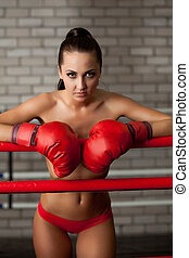 Attractive brunette posing topless in boxing ring