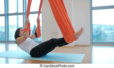 Attractive brunette practicing yoga hammock in studio indoors.