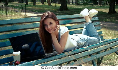 attractive brunette smiling lies on a bench and looking at laptop