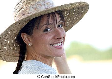 Attractive brunette wearing straw hat