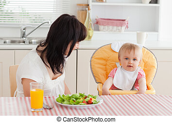 Attractive brunette woman having a meal with her baby while sitting in the kitchen
