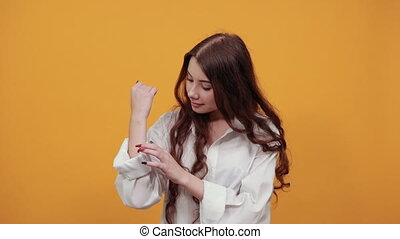 Attractive brunette woman in fashion white shirt showing hands, wrists isolated on orange background in studio. People sincere emotions, lifestyle concept.
