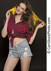 Attractive brunette woman in jeans shorts and plaid shirt
