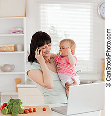 Attractive brunette woman on the phone while holding her baby in her arms in the kitchen