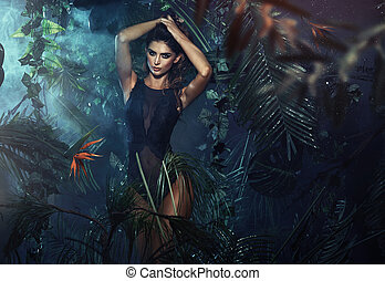 Attractive brunette woman posing in the jungle