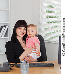 Attractive brunette woman posing while holding her baby on her knees in the office