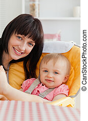 Attractive brunette woman posing with her baby while sitting