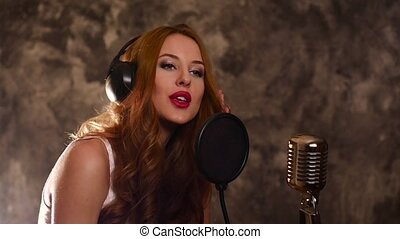Attractive brunette woman recording a song in music studio,slow motion, close up