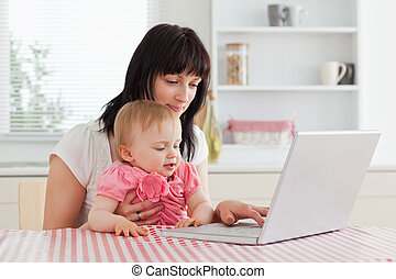 Attractive brunette woman showing her laptop to her baby while sitting in the kitchen