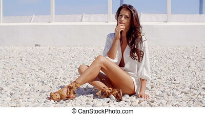 Attractive Brunette Woman Sitting on Stone Beach