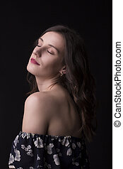 Attractive brunette woman with closed eyes at studio