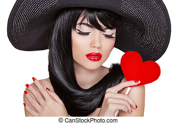 Attractive brunette woman with holiday makeup holding red heart isolated on white background