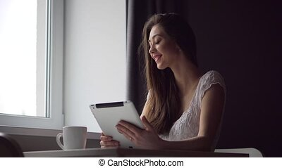 Attractive Brunette Woman Works with Tablet pc