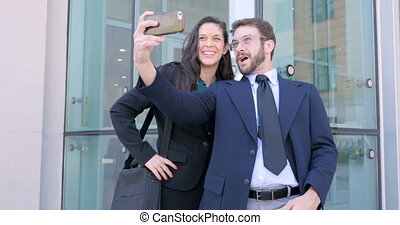 Attractive business couple take selfie with cell phone outside office building