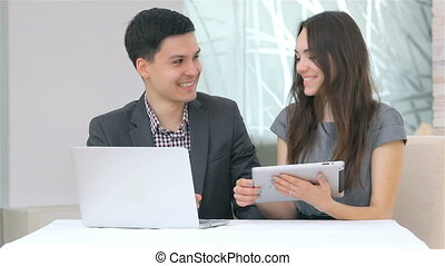 Attractive business man and woman discussing collating data on the tablet