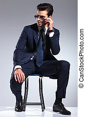 Attractive business man sitting on a stool