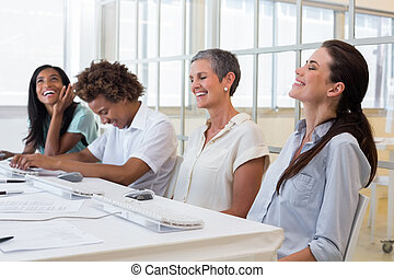 Attractive business people laughing during a business meeting