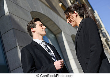 Attractive business people talking outside of company building. Couple working.